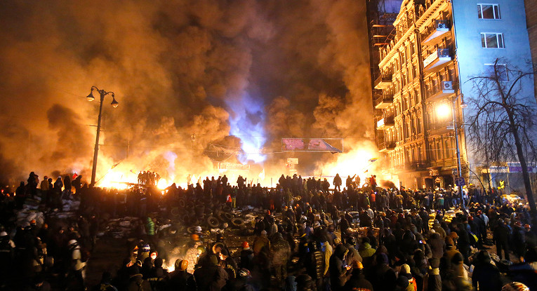 "FILE - In this file photo taken on Saturday, Jan.  25, 2014,  smoke and fireballs rise during clashes between protesters and police in central Kiev, Ukraine. The ""Heavenly Hundred"" is what Ukrainians in Kiev call those who died during months of anti-government protests in 2013-14. The grisliest day was a year ago Friday _ Feb. 20, 2014 _ when sniper fire tore through crowds on the capital"